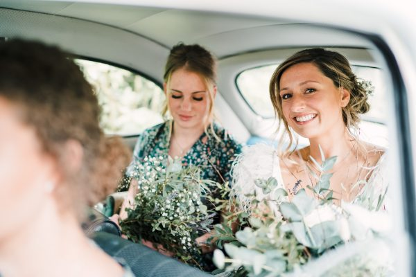 bride and bridal party in the back of the wedding car