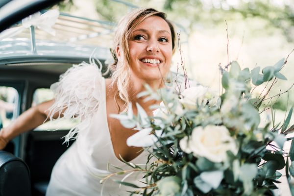 bride exits the wedding car holding her bouquet of flowers