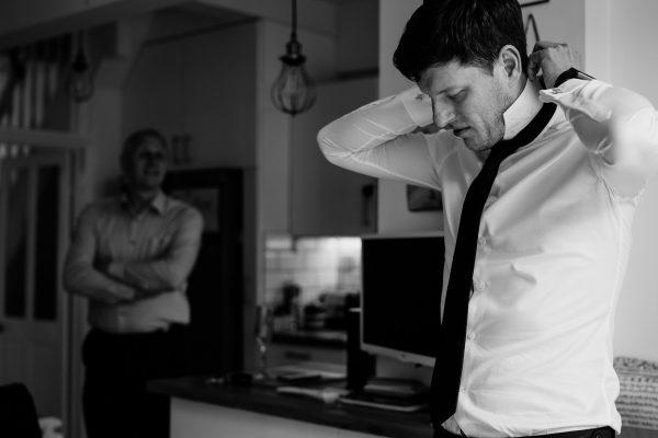 groom puts tie on
