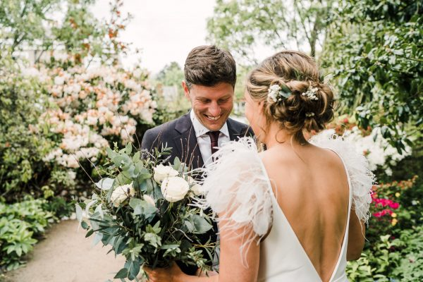 groom sees his bride for the first time in the gardens of the venue