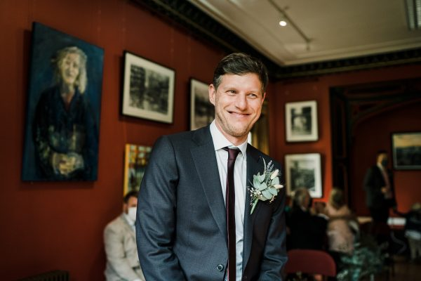 groom stands at the front of the ceremony room at the Didsbury Parsonage