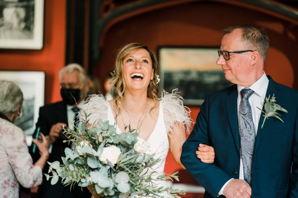 bride and brides father walk up the aisle to meet her groom and laughs